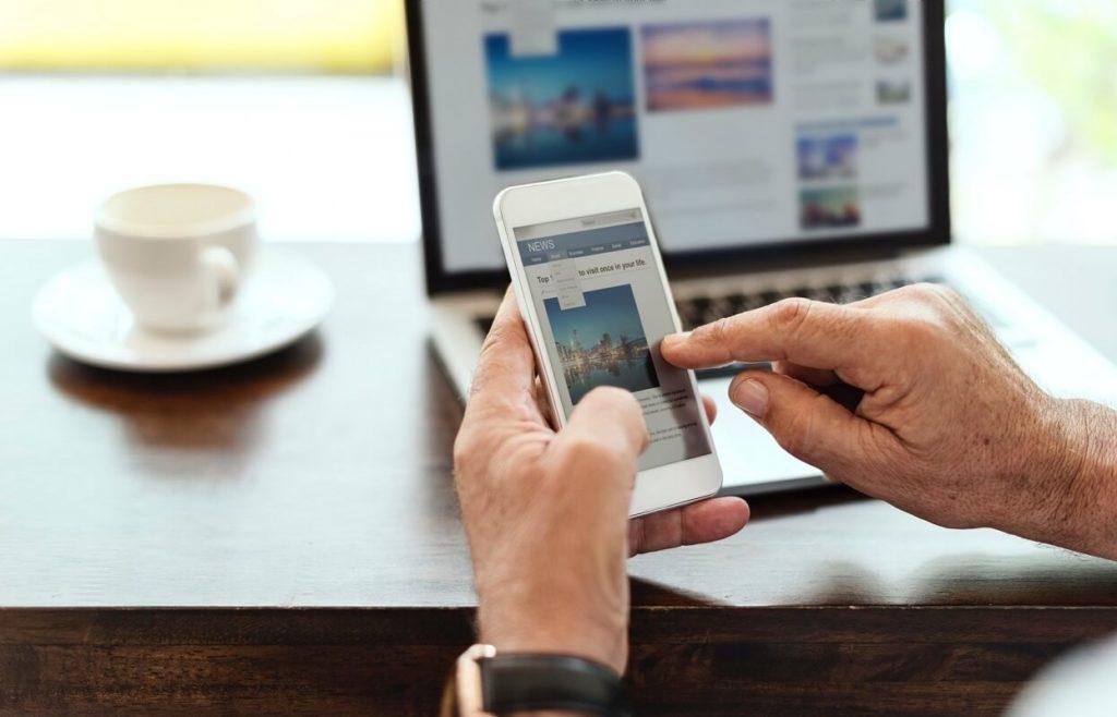Iäkäs henkilö kokeilee verkkopankin käyttöä kännykällä