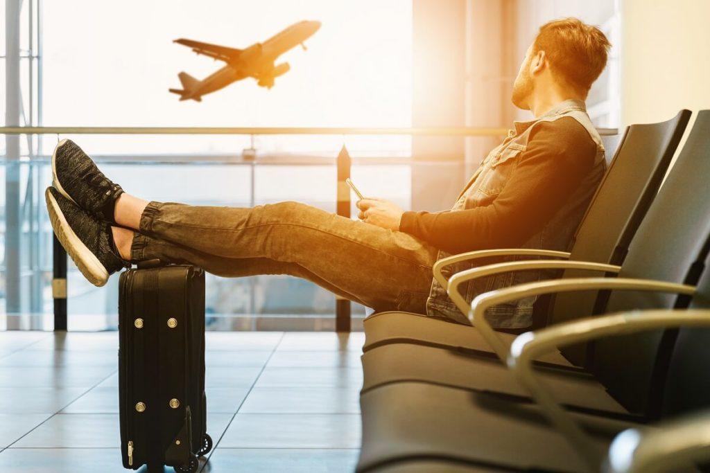 Mies istuu lentokentällä ja katsoo ikkunasta lentokoneen nousua.