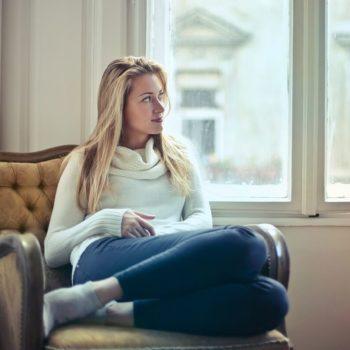 Vaaleahiuksinen nuori nainen istuu ikkunan äärellä vuokra-asunnossa, johon hän on juuri muuttanut