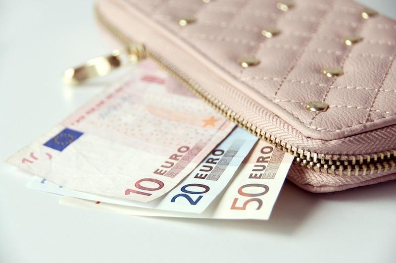 Vaaleanpunainen lompakko ja euron seteleitä. Yhdistämällä lainasi säästät rahaa