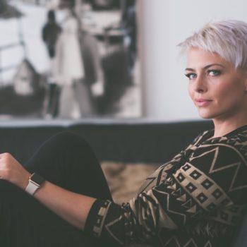 Lyhythiuksinen nuori nainen istuu sohvalla ja vastaa kysymyksiin lainojen kilpailutuksesta