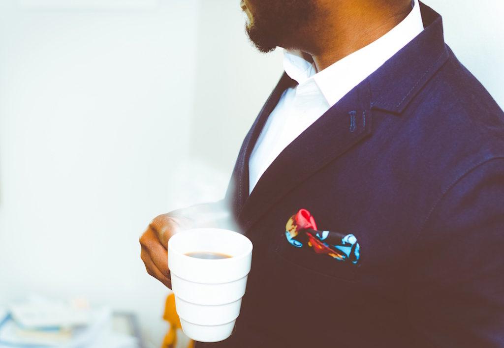 Tyylikäs mies pitelee kahvikuppia kädessään ja suunnittelee kilpailuttavansa lainansa