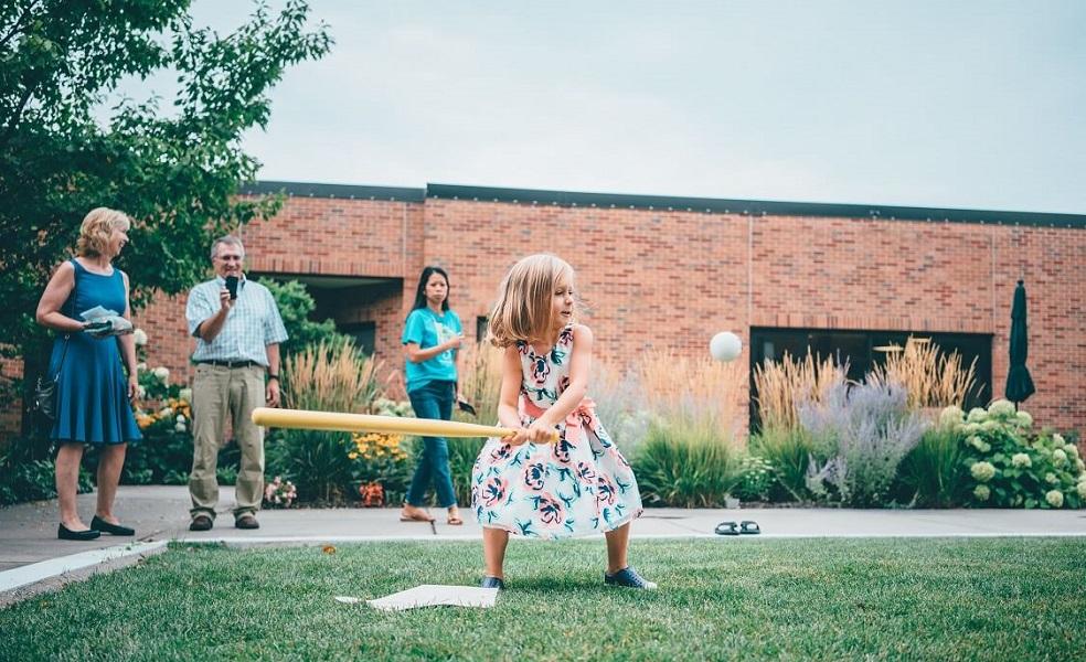 Pieni tyttö pelaa pesäpalloa perheensä uuden asunnon takapihalla hänen perheensä katsellessa hymyillen