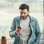 Nuori mies seisoo ikkunan äärellä ja nostaa kännykkänsä avulla uuden pikavipin