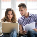 Huolestuneen näköinen pariskunta istuu sohvallaan ja katsovat kannettavalta tietokoneelta saamaansa hylättyä lainapäätöstä