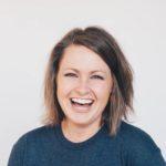 Iloinen nainen nauraa kameralle yhdistettyään lainansa