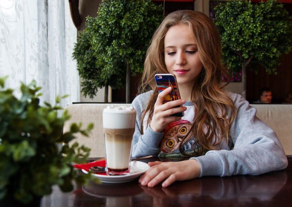 Nuori tyttö nostaa pikavipin kännykällään kahvilassa