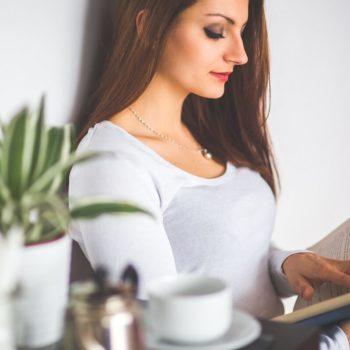 Kaunis nainen lukee kirjaa tyytyväisenä ratkaisuunsa yhdistää lainansa