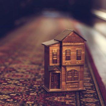 Koristeellinen puinen leikkitalo ruskealla matolla