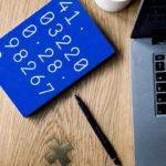 Sininen laskuri, kannettava tietokone ja kynä aseteltuna pöydälle