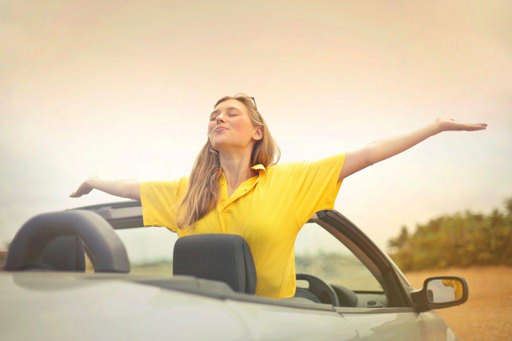 Huolettoman näköinen nuori nainen istuu autossaan tyytyväisenä saavutettuaan taloudellisen riippumattomuuden