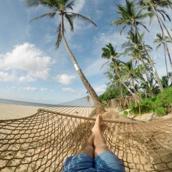Mies makaa huoletta riippumatossa etelän rannalla saavutettuaan taloudellisen riippumattomuuden