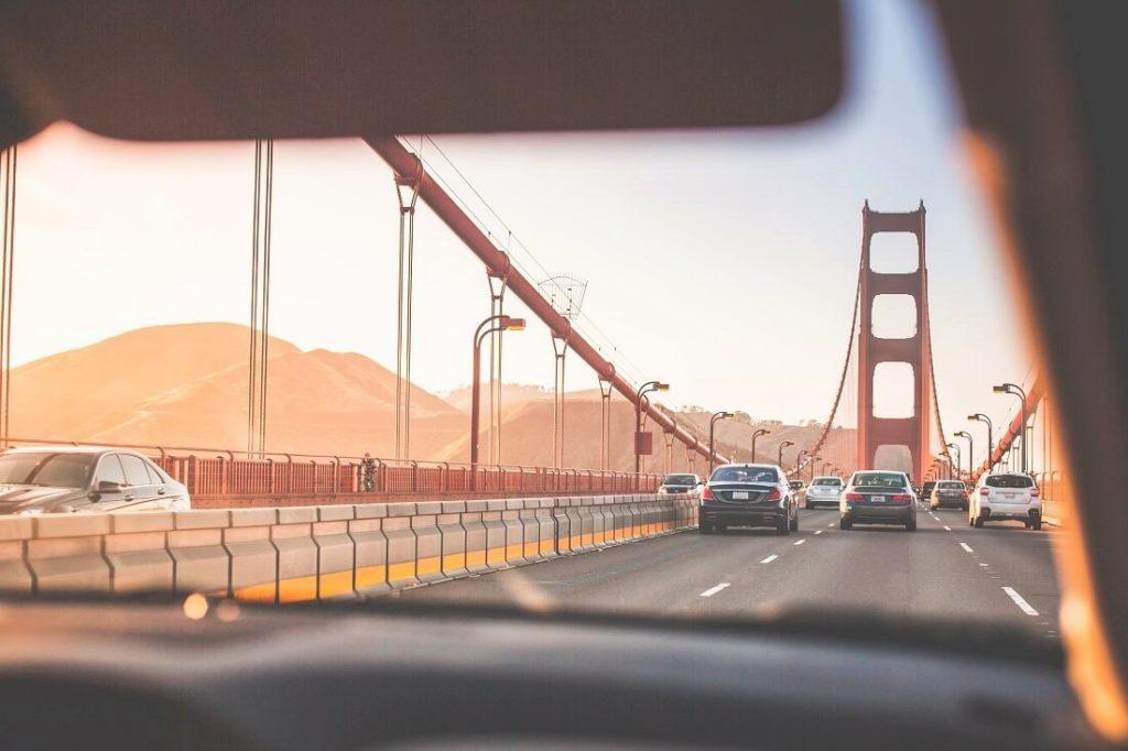 Auto ajamassa Golden Gate Bridgen ylitse auringonlaskussa.