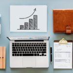 Kuva työpöydästä, jolla on tietokone, salkku, kahvikuppi, papereita ja kaava kuvaamassa sijoitusten kasvua.