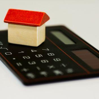 Kuvassa pieni puinen talo laskurin päällä.