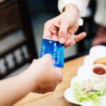 Henkilö maksaa aamiaisensa luottokortilla.