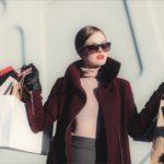 Kaunis nuori nainen kantaa kauppakasseissa tekemiään ostoksia.