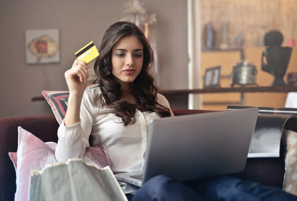 Nuori tyttö tekee nettiostoksia luottokortilla.
