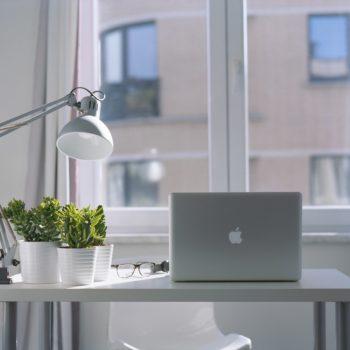 Täysi työpöytä kerrostalo asunnon ikkunan äärellä.