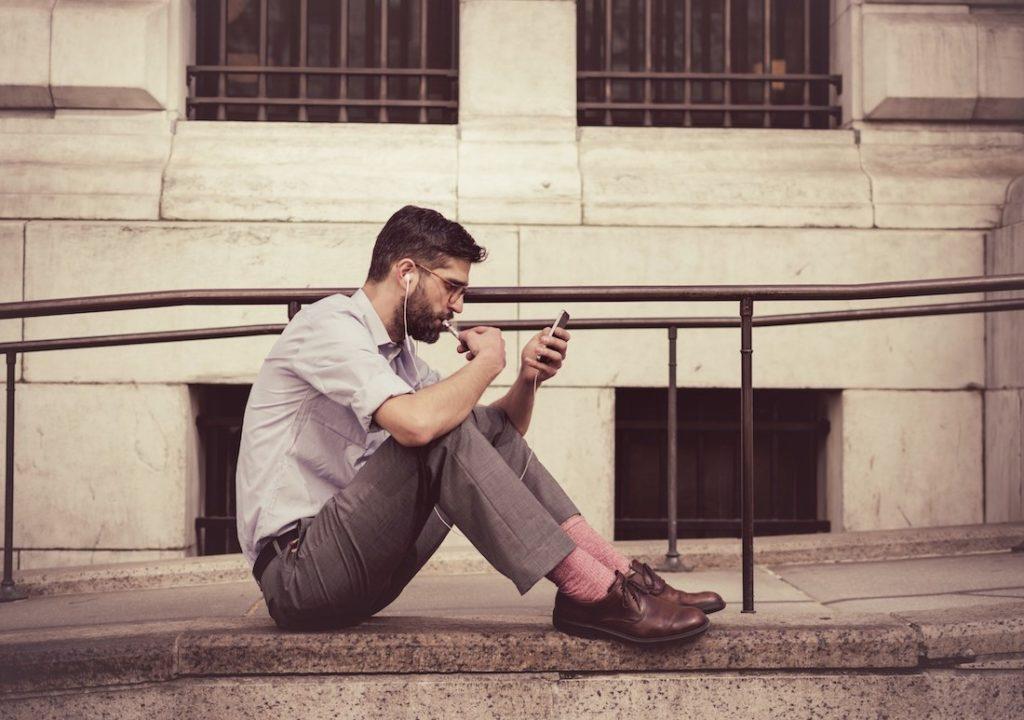 Nuori silmälasipäinen mies opiskelee asuntosijoittamista kuuntelemalla podcastia