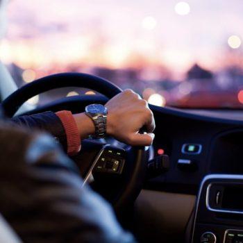 Mies ajaa autolla työpaikallensa