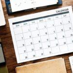 Työpöytä, jolla on kuukausikalenteri, kannettava tietokone ja kännykkä