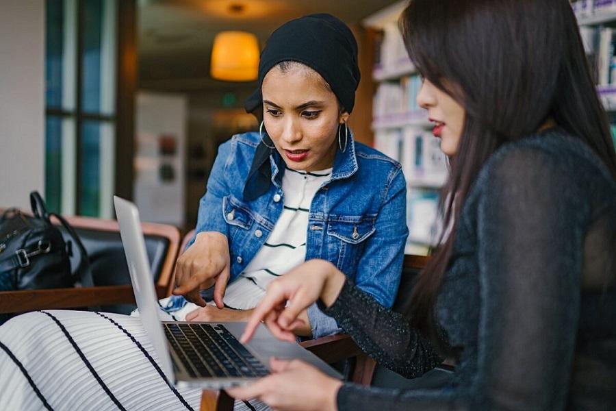 Kaksi nuorta naista tietokoneen äärellä opiskelemassa sijoittamista