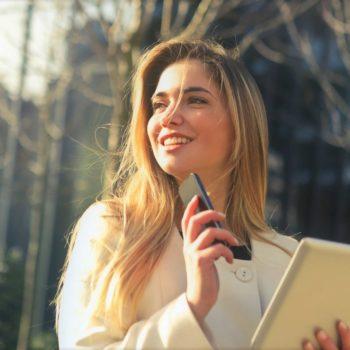 Nuori asuntosijoittaja hymyilee kännykkä kädessään tehtyään kaupat asunnosta