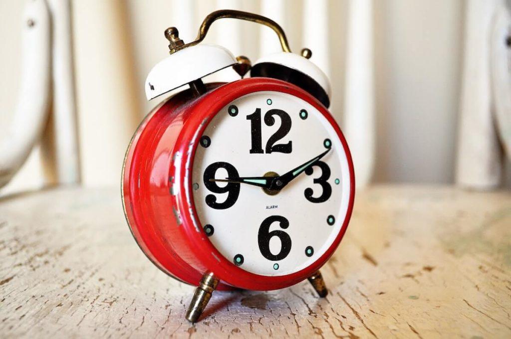 Punainen herätyskello ottamassa aikaa, kun hakija tarvitsee lainan heti
