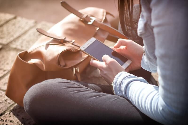Nainen istuu lattialla älypuhelin kädessään ja kilpailuttaa liittumän netissä