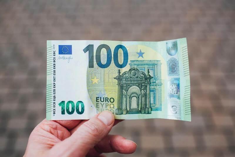 Henkilö on ottanut helpon vipin ja pitää kädessään 100 euron seteliä