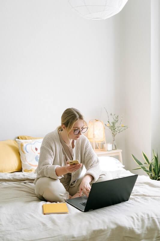 Nainen istuu sängyllä tietokoneen edessä ja tunnistautuu mobiilivarmenteella kännykällä