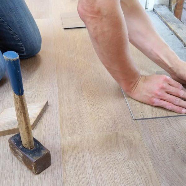 Henkilö asentaa vaaleaa lattiaa työkalujen kanssa