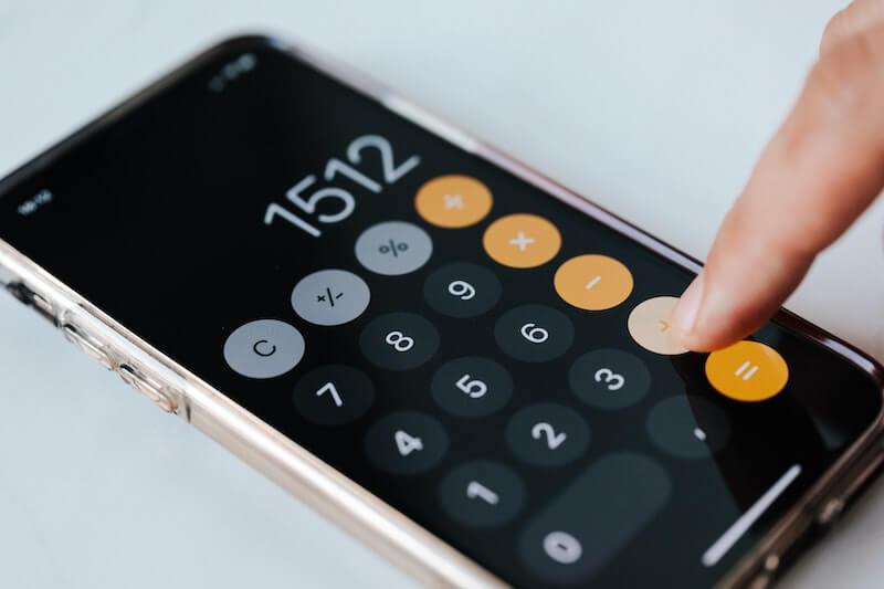 Henkilö laskee puhelimella vanhojen lainojen kuluja hakiessaan yhdistelylainaa