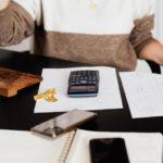 Nainen istuu pöytäkoneen ääressä, edessään lehtiö, papereita, kaksi älypuhelinta ja laskin ja laskee, mikä on halvin sähkö