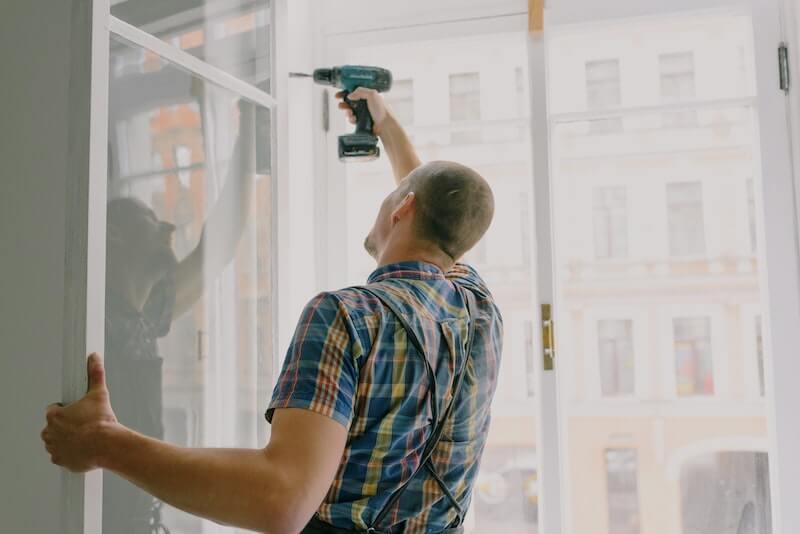 Mies tekee kotitalousvähennykseen kuuluvaa remonttia ja asentaa ikkunaa