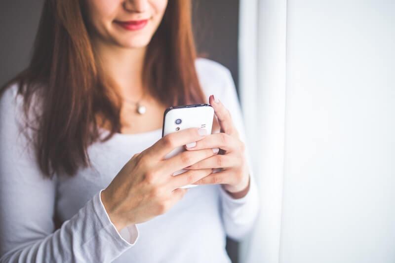 Seisova naishenkilö kädessään älypuhelin, jossa on Moi liittymä