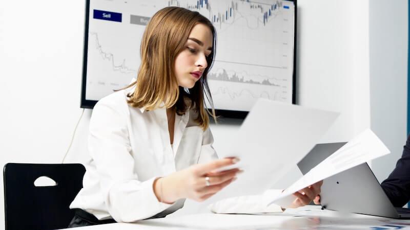 Nainen istuu pöydän ääressä tarkastellen osinkokalenteria iso kaavio taustallaan