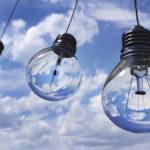 Kolme hehkulamppua roikkuu sinivalkoista taivasta vasten
