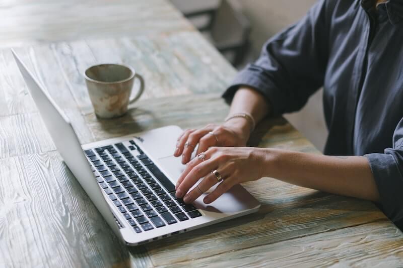 Naishenkilö kannettavan tietokoneen äärellä kirjautumassa tulorekisteriin