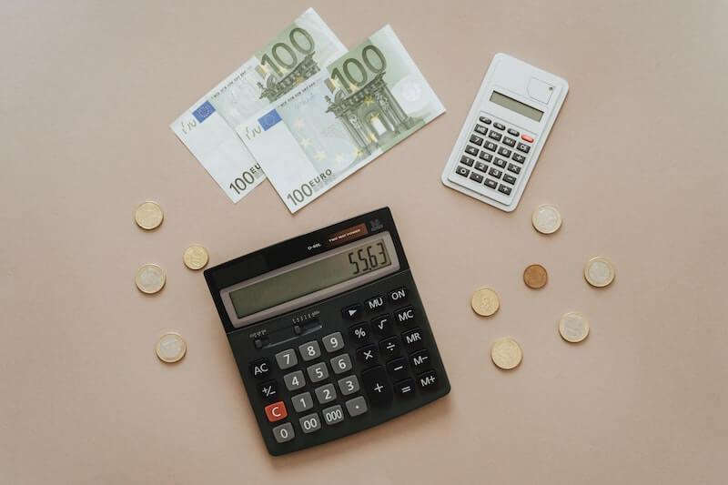 Kaksi taskulaskinta, joilla voi laskea ALV:in sekä kolikoita ja seteleitä pöydällä.