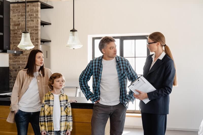 Perhe, jolla on asuntolainan lainalupaus, keskustelee välittäjän kanssa asuntonäytöllä