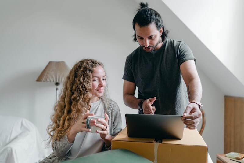 Nainen ja mies ovat hakeneet asuntolainaa ja katsovat lainatarjousta koneelta
