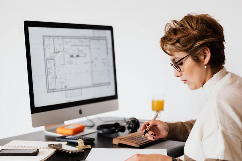 Kevytyrittäjänä toimiva nainen tietokoneen edessä tekemässä muistiinpanoja