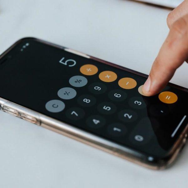 Henkilö laskee kotitalousvähennyslaskurilla puhelimella vähennyksen määrää