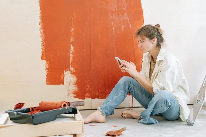 Maalaustöissä oleva nainen istuu lattialla kännykkä kädessään ja laskee kotitalousvähennyslaskurilla