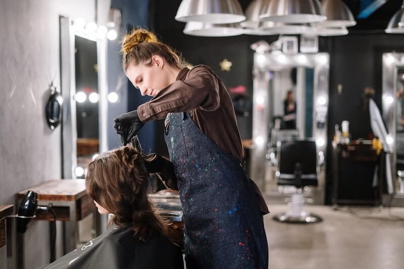 Kampaaja, jolla on yel-vakuutus, leikkaa asiakkaan hiuksia
