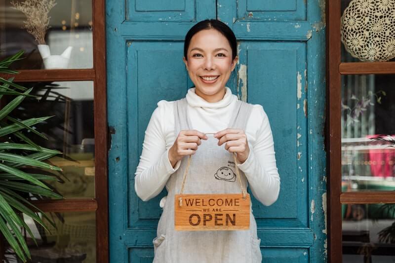"""Hymyilevä yrityksen perustanut nainen liikkeen edessä kädessään """"Welcome we are open"""" -tekstillä varustettu kyltti."""