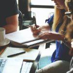 Kolme henkilöä pöydän ääressä kokoustamassa ja tekemässä yrityksen perustamisilmoitusta