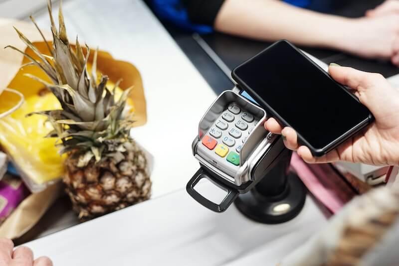 Henkilö maksaa ostoksia kassalla MobilePayllä.